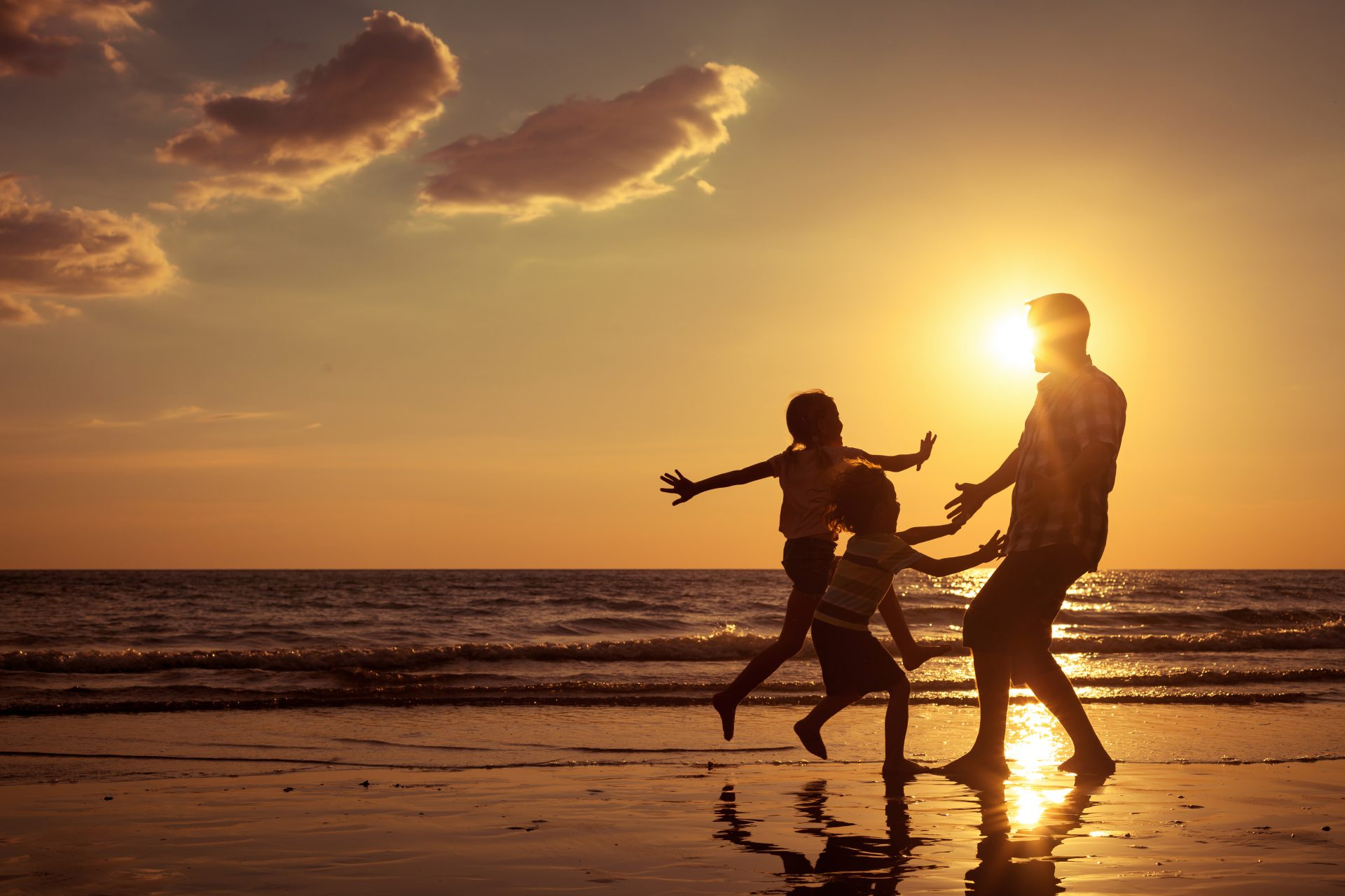 Family playing on beach at sunset
